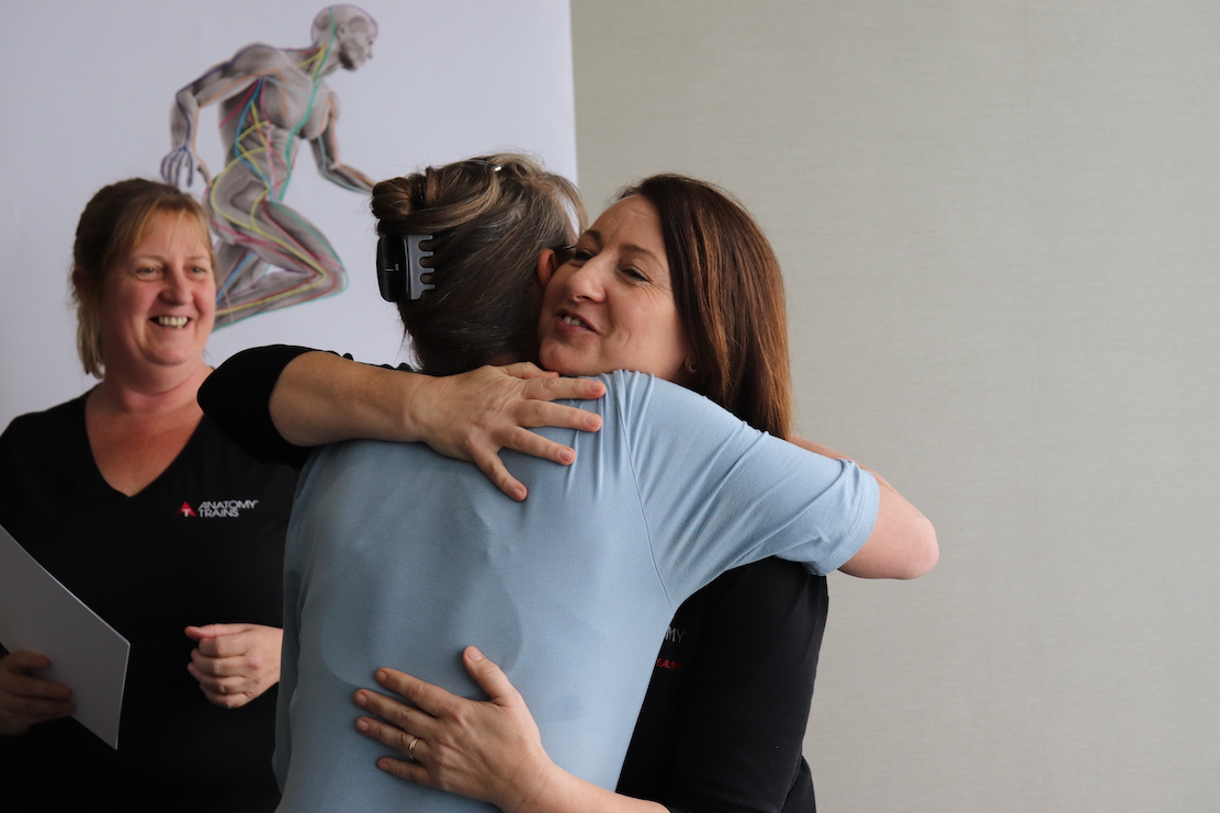 Two people hugging while another person smiles in background.